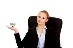 坐椅子和拿着房子的微笑的女商人塑造 免版税库存图片