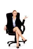 坐椅子和拿着房子的微笑的女商人塑造 库存照片