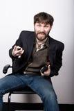 坐椅子和拿着枪的夹克和牛仔裤的快活的有胡子的人 匪徒概念 库存照片