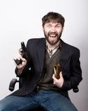 坐椅子和拿着枪的夹克和牛仔裤的快活的有胡子的人 匪徒概念 库存图片