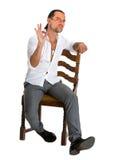 坐椅子和显示好标志的英俊的人 免版税库存图片