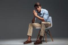 坐椅子和看照相机的体贴的英俊的年轻人 免版税库存图片