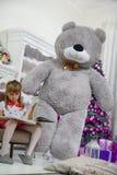坐椅子和读书的小女孩,给了她在圣诞节 免版税库存照片