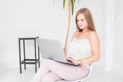 坐椅子对白色墙壁和工作在膝上型计算机的一个年轻白肤金发的女孩的画象 库存图片