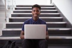 坐楼梯和使用膝上型计算机的男性高中生画象 库存图片