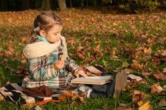 坐毯子和读一本书的一个小女孩在公园,很多金黄下落的叶子  库存图片