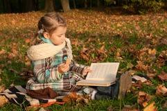 坐毯子和读一本书的一个小女孩在公园,很多金黄下落的叶子  免版税库存照片