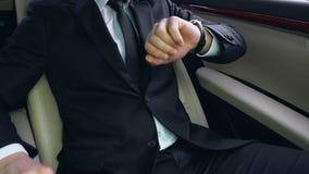 坐汽车后座和看手表的商人,困住在交通 影视素材