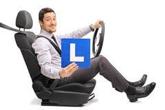 坐汽车座位和拿着L标志的人 免版税库存图片