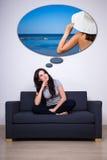 坐沙发和作梦关于夏天的愉快的妇女 库存照片