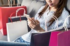 坐沙发和使用巧妙的电话的愉快的亚裔妇女 免版税库存图片