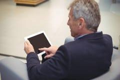 坐沙发和使用数字式片剂的殷勤商人 免版税图库摄影