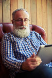坐沙发和使用片剂个人计算机的有胡子的人 免版税图库摄影