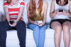 坐沙发和使用电话的朋友 免版税图库摄影