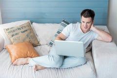 坐沙发和使用膝上型计算机的英俊的年轻人 免版税库存图片