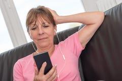 坐沙发和听到与她的MOBIL电话的音乐的妇女 免版税库存照片