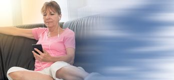 坐沙发和听到与她的MOBIL电话的音乐,光线影响的妇女 免版税库存照片