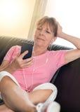 坐沙发和听到与她的MOBIL电话的音乐,光线影响的妇女 库存图片