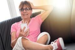 坐沙发和听到与她的MOBIL电话的音乐,光线影响的妇女 库存照片