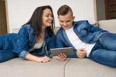 坐沙发和在家使用数字式片剂的愉快的家庭 库存照片