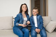 坐沙发和在家使用数字式片剂的愉快的家庭 免版税库存照片