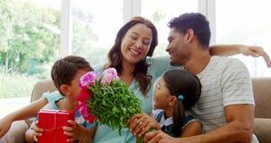 坐沙发和拥抱在客厅的愉快的家庭 股票录像