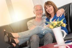 坐沙发和拥抱,光线影响的愉快的资深夫妇 免版税库存照片