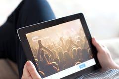 坐沙发和拿着与App慌张的妇女iPad在t 免版税库存图片