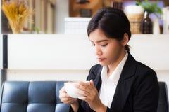 坐沙发和看杯子热的咖啡的一个美丽的亚裔女商人在她的手上 免版税图库摄影