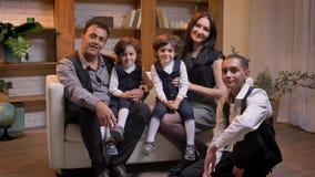 坐沙发和观看入与微笑的照相机的阿拉伯家庭在客厅 影视素材