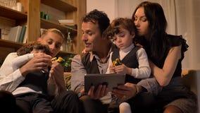 坐沙发和观看入片剂的阿拉伯家庭画象在舒适大气的客厅 股票录像
