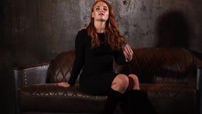 坐沙发,哀伤地笑和看在客厅的红头发人妇女 影视素材