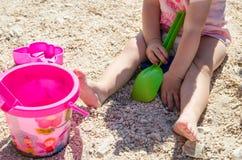 坐沙子和使用与塑料玩具的小女孩 免版税库存图片