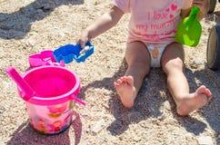 坐沙子和使用与塑料玩具的小女孩 免版税图库摄影