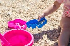 坐沙子和使用与塑料玩具的小女孩 库存图片