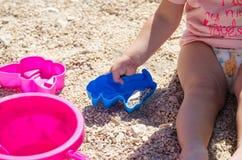 坐沙子和使用与塑料玩具的小女孩 免版税库存照片