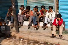 坐沿街道的年轻人在德里,印度 免版税图库摄影