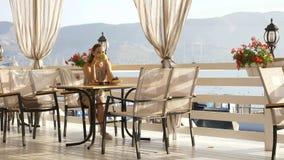 坐注视海海湾的美丽的景色年轻俏丽的妇女在咖啡馆 免版税图库摄影