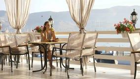 坐注视海海湾的美丽的景色年轻俏丽的妇女在咖啡馆 免版税库存照片