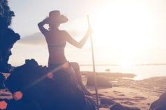 坐海岛用竹棍子和看海洋的妇女 库存照片