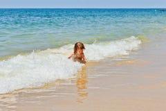 坐海滩和使用在波浪的小女婴 图库摄影