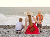 坐海滩和观看波浪的妈妈和两个儿子 回到视图 库存图片