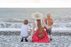 坐海滩和观看波浪的妈妈和两个儿子 回到视图 免版税库存照片