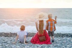 坐海滩和观看波浪的妈妈和两个儿子 回到视图 库存照片
