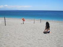 坐海滩和调查距离的女孩 免版税库存照片