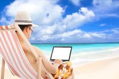 坐海滩睡椅和使用膝上型计算机的轻松的人 免版税库存图片