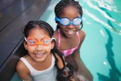 坐游泳池边的逗人喜爱的小孩 免版税图库摄影