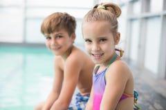 坐游泳池边的逗人喜爱的矮小的兄弟姐妹 库存图片