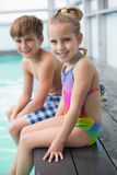 坐游泳池边的逗人喜爱的矮小的兄弟姐妹 免版税库存照片