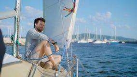 坐游艇和微笑对照相机的美满的年轻人 股票录像